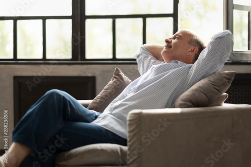 Spoed Foto op Canvas Ontspanning Happy senior hispanic man relaxing on sofa at home