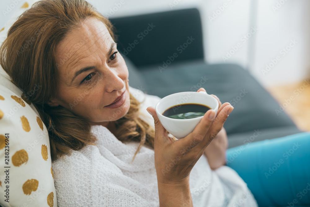 Fototapeta close up shot of beautiful middle aged woman drinking coffee or tea