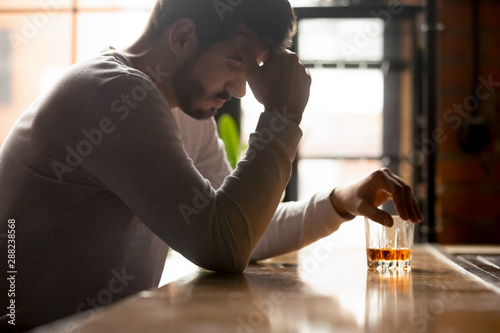 Poster de jardin Bar Stressed drunk man sitting alone with glass of whiskey in bar