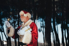Cheerful Senior Man In Costume Of Santa Claus Standing With Present And Bell In Gloved Hands Looking Away On Nature Background