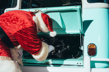 Unrecognizable Person In Red And White Costume Of Santa Claus Inspecting Engine Of Vintage Green Van On Sunny Day