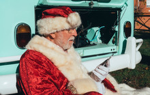 Side View Of Senior Man In Costume Of Santa Claus Speaking On Mobile Phone While Sitting By Van With Open Engine Compartment