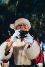 Smiling Senior Man In Costume Of Santa Claus Standing And Taking Photos By Camera On Nature Background Looking Away