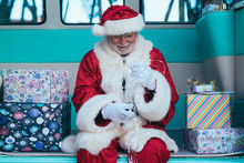 Senior Man In Costume Of Santa Claus Sitting In Retro Van Between Presents And Holding Garland In Gloved Hands