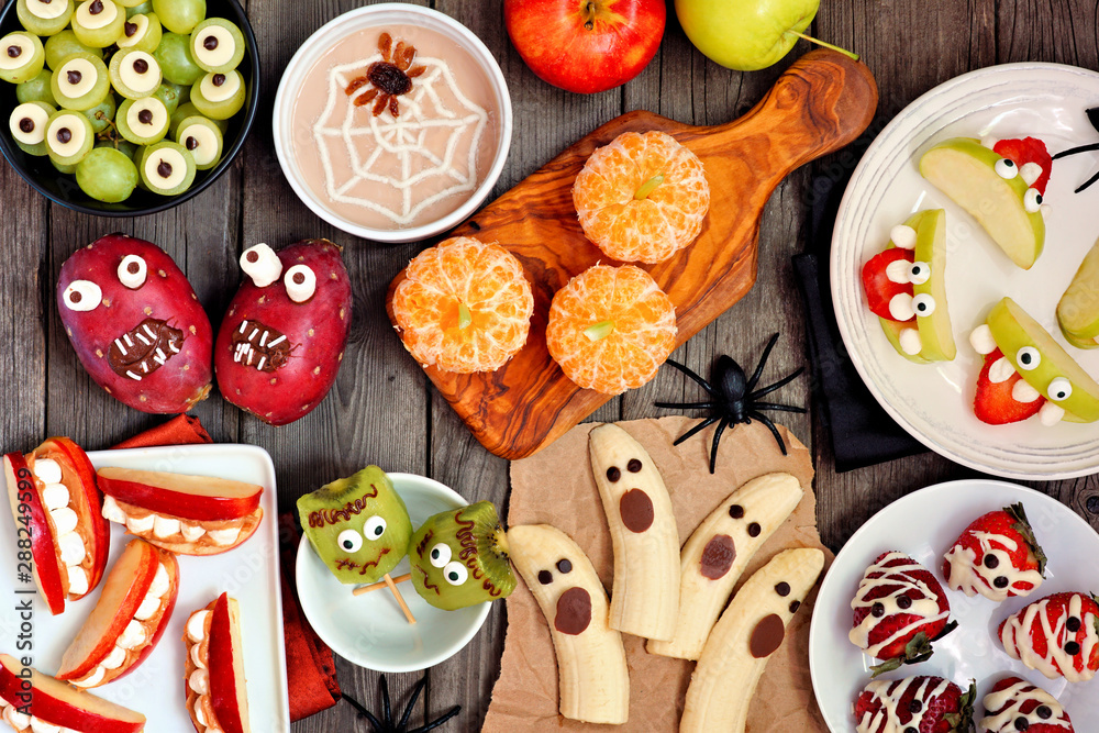 Fototapety, obrazy: Healthy Halloween fruit snacks. Selection of fun, spooky treats. Top view table scene over a rustic wood background.
