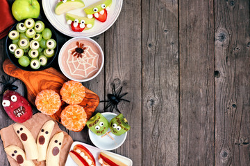 Healthy Halloween fruit snacks. Assortment of fun, spooky treats. Top view side border over a rustic wood background with copy space.