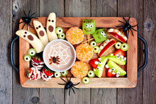 Healthy Halloween Fruit Snacks. Tray Of Fun, Spooky Treats. Top View Over A Rustic Wood Background.
