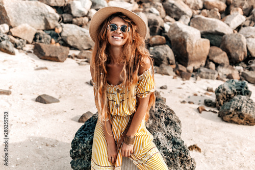 Fototapeta beautiful young stylish boho woman in elegant dress outdoors wearing hat and sun