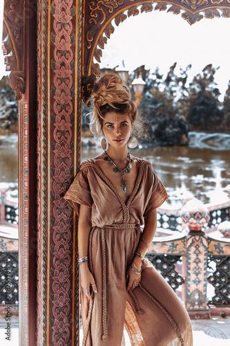 beautiful young boho woman in elegant dress at the ancient temple background