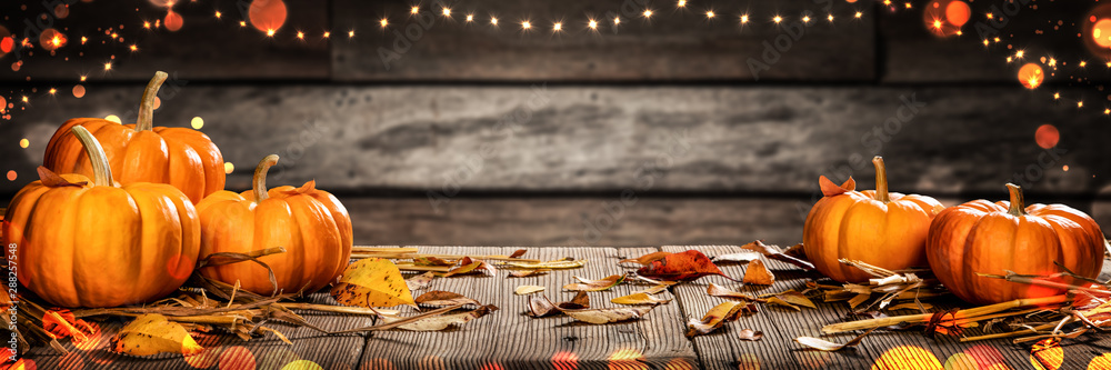 Fototapeta Mini Thanksgiving Pumpkins And Leaves On Rustic Wooden Table With Lights And Bokeh On Wood Background - Thanksgiving / Harvest Concept