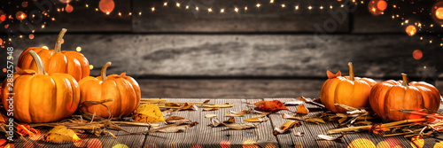 fototapeta na drzwi i meble Mini Thanksgiving Pumpkins And Leaves On Rustic Wooden Table With Lights And Bokeh On Wood Background - Thanksgiving / Harvest Concept