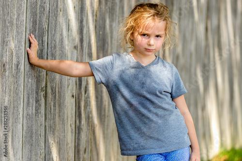 Fototapety, obrazy: Little girl holding self up against wooden fence