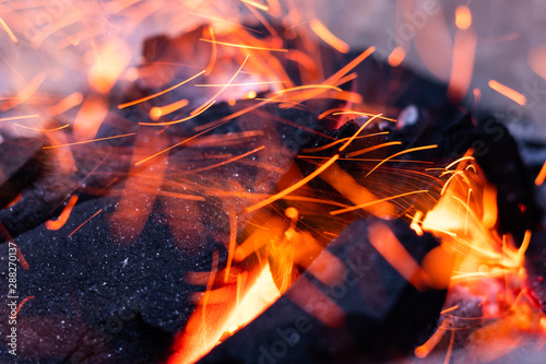 Fotografie, Tablou Close up view of glowing flying sparks hot fire flame from hot bonfire charcoal