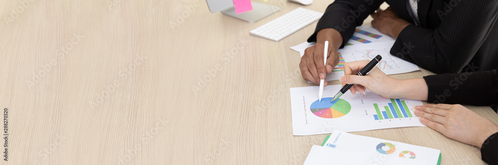 Fototapeta Close up Hand of businessman in black suit talking  planning business strategy. They pointing paperwork Marketing plan researching. Business teamwork, brainstorming concept. with copy space