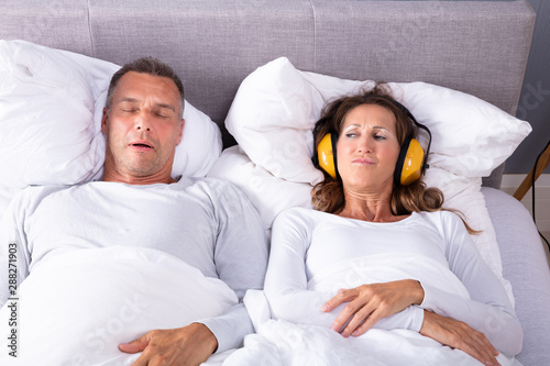Woman Covering Her Ears With Headphones While Man Snoring Canvas Print