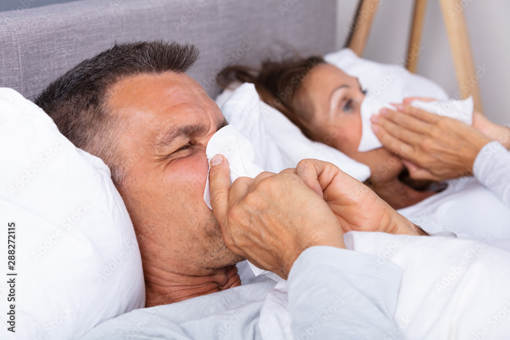 Fototapeta Sick Couple Lying On Bed Blowing Their Nose