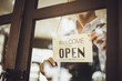 canvas print picture - Store owner turning open sign broad through the door glass and ready to service.