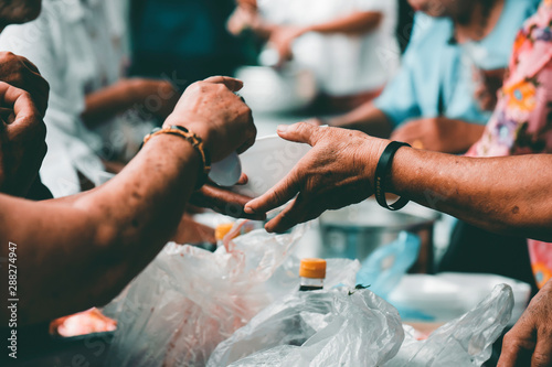 Tablou Canvas Giving food to beggars to help reduce hunger with concern: the concept of food n