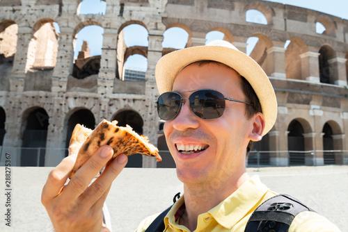 Obraz na plátne  Man Eating Italian Pizza Near Colosseum