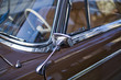 Close up of shiny chrome rear view mirror of classic car.