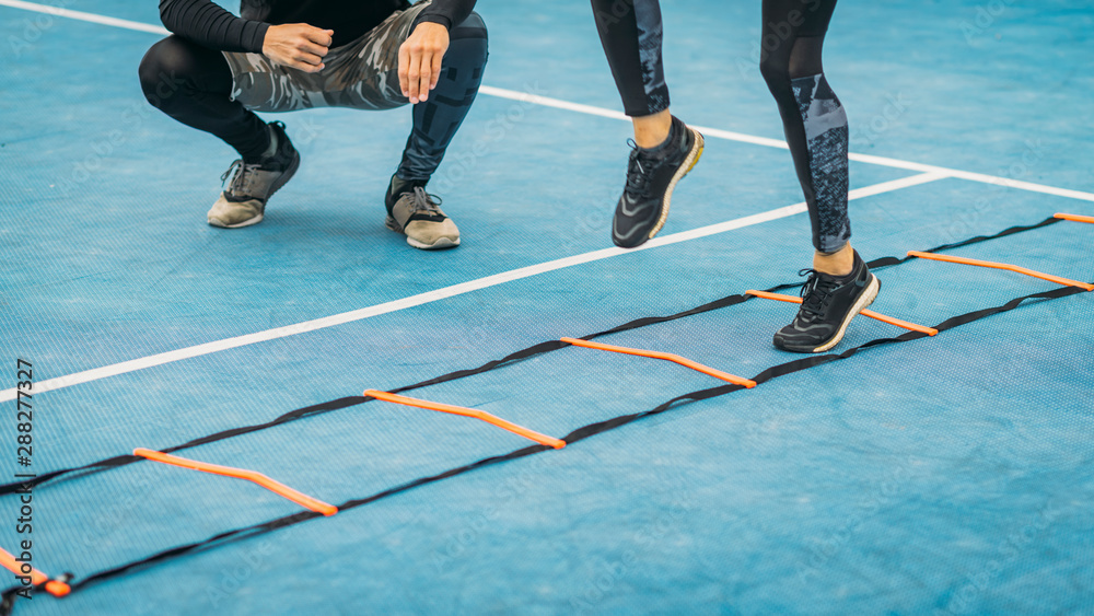 Fototapeta Young Woman Exercise using Agility Ladder, working with Fitness Coach