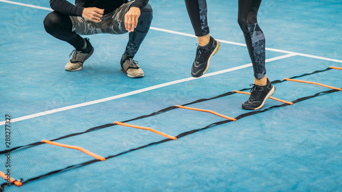 Young Woman Exercise using Agility Ladder, working with Fitness Coach Wallpaper Mural