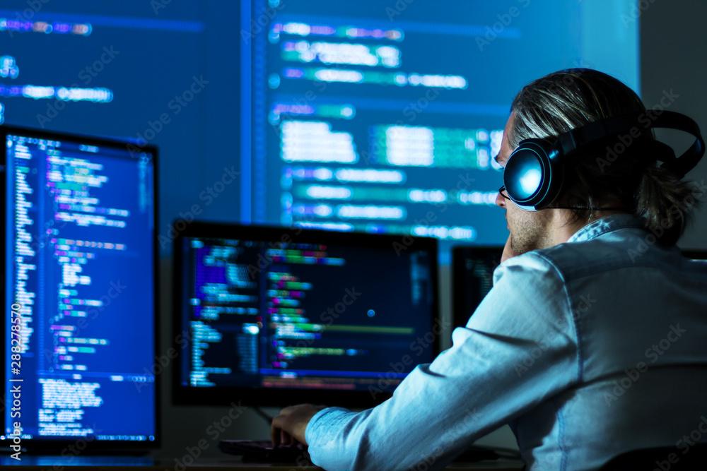 Fototapeta Software developer freelancer man male in headphones work with program code C++ Java Javascript on wide displays at night Develops new web desktop mobile application or framework. Projector background