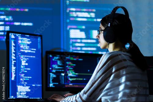 Fototapety, obrazy: Software developer freelancer woman female in glasses work with program code C++ Java Javascript on wide displays at night Develops new web desktop mobile application or framework Projector background