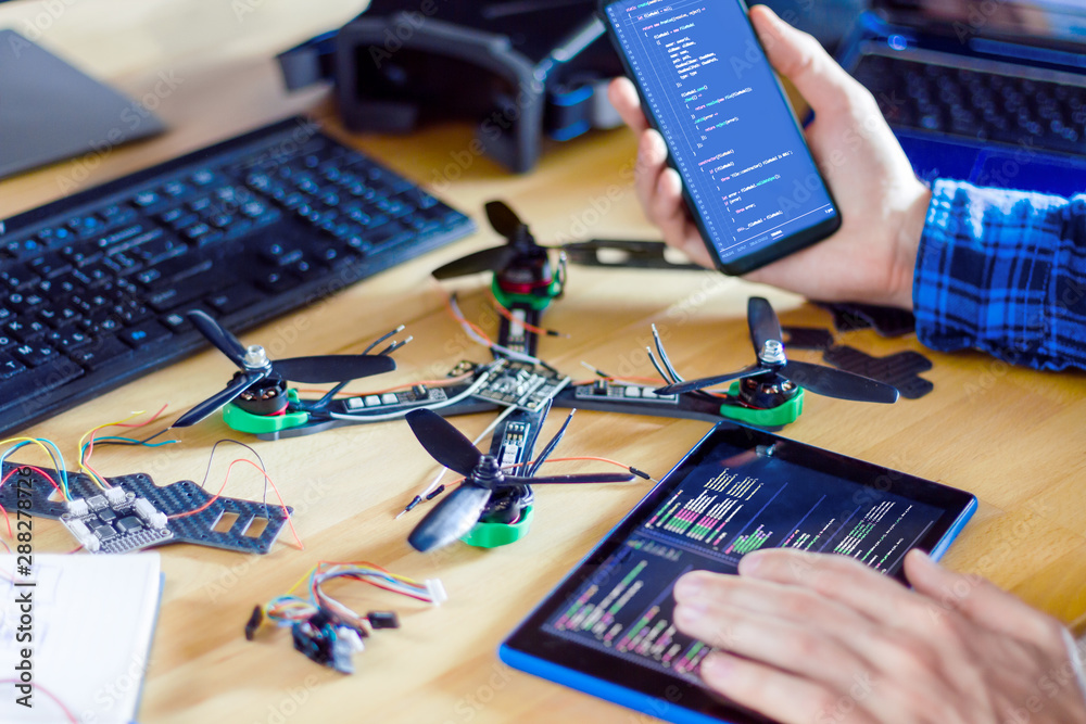 Fototapety, obrazy: Closeup programmer hand are holding smartphone and tablet with program code of software on screen for controlling FPV drone. Man developer is building quadcopter from kit with microcontrollers.