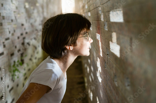Fotografiet  Child looking through the bricks inside the Nazari Wall