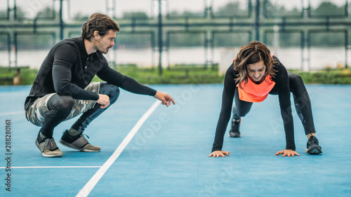 Fotografie, Tablou Young Female Athlete Exercising with Personal Fitness Trainer
