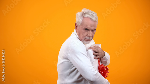Greedy male pensioner embracing giftbox and seriously looking on camera, avarice Canvas Print