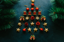 Winter Holidays. Flat Lay Of Abstract Christmas Tree Of Red And Golden Ornaments On Dark Blue Textured Background.