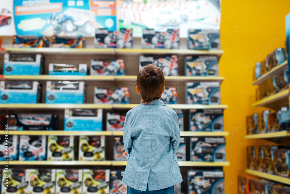 Fototapety, obrazy: Little boy at the shelf in kids store, back view