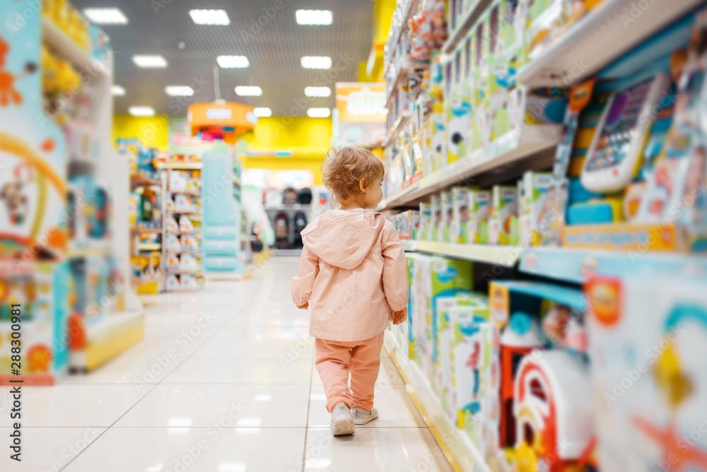 Fototapety, obrazy: Little girl choosing toys in kids store