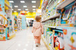 canvas print picture - Little girl choosing toys in kids store
