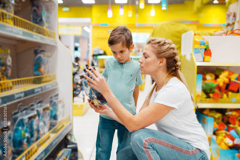 Fototapety, obrazy: Happy mother with her little son in kids store