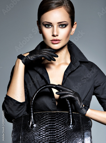 Beautiful woman in black  holds fashion handbag Obraz na płótnie