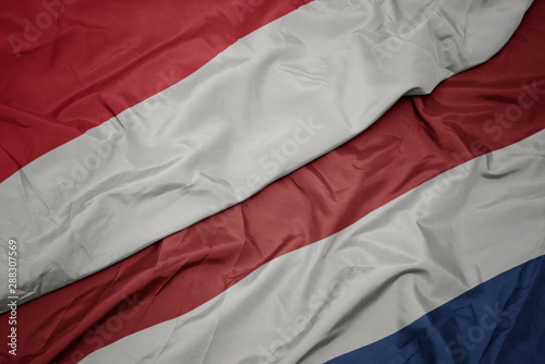 waving colorful flag of netherlands and national flag of indonesia.