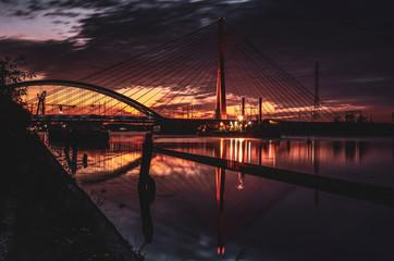 Wschód słońca nad rzeką, krajobraz miejski, mosty.