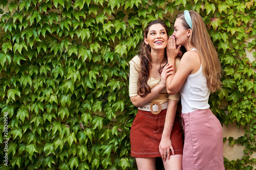 Young beautiful girls dressed in retro vintage style enjoying the old european c Wallpaper Mural