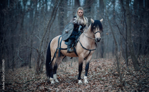 Foto  Viking warrior female ridding a horse at twilight autumn forest - Medieval movie