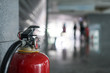 Close up of Fire extinguisher. Interior of Building in public place.