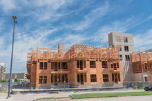 Wooden Apartment Complex Under Construction Near Completed Condos And Commercial Building