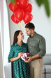 Young couple with air balloons and gift box at home. Celebration of Saint Valentine's Day