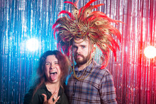 Fun, Holiday, April Fools Day And Strange People Concept - Crazy Young Woman And Funny Man In Carnival Hat Looking Surprised
