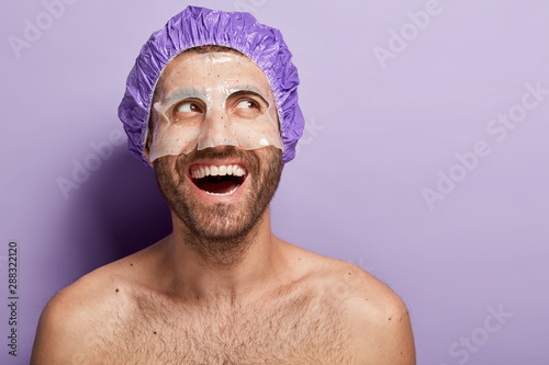 Fotografía  Happy positive young man applies facial mask, wears shower cap, laughs positively, has naked body, dark bristle, enjoys spa treatment, isolated over purple background, feels relaxed