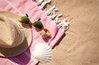 Flat lay composition with stylish beach accessories on sand, space for text