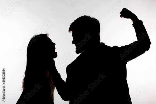 Photo Domestic violence and abuse concept - Silhouette of man beating defenseless woma