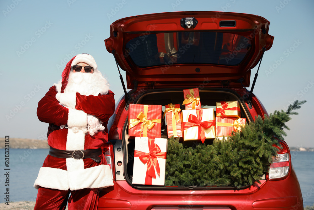 Fototapety, obrazy: Authentic Santa Claus near car with open trunk full of presents and fir tree outdoors